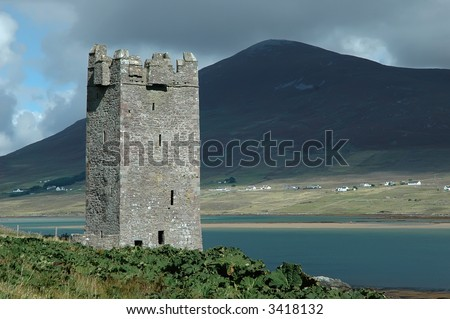 An old castle tower ruin on Achill Island (Ireland) on a sunny day. In the background a large hill on the mainland with an Irish village.