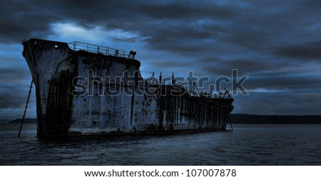 An old cement freighter rests peacefully as a breakwater for a log pond.