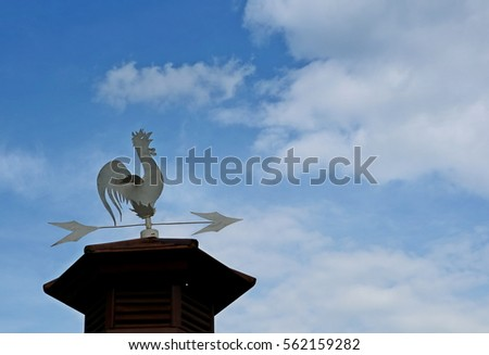 An old chicken metal weather vane, or weathercock on top roof with beautiful blue sky with white cloud and copy space #562159282