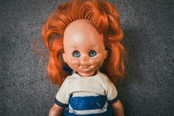 An old children's doll for girls with a gray background behind. A children's toy from the time of the communist system in Eastern Europe. Old plastic female doll. The concept of old children's toys