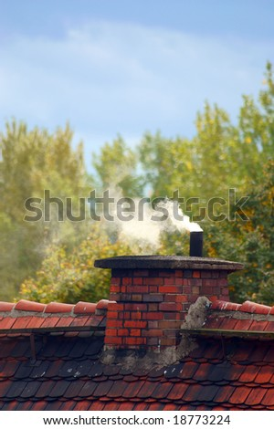 An old chimney and smoke on a private house