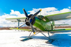 An old classic airplane. The biplane stands in the snow on skis in winter against the sky - preparing to fly. Retro airplane at the airport in nature. Winter air transportation of passengers and cargo