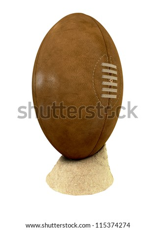 An old classic leather rugby ball with laces and stitching placed on a small pile of beach sand on an isolated background