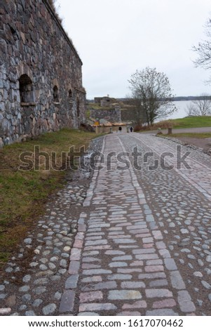 An old cobblestone road in the historic island of Suomenlinna (Sveaborg) among historical granite fortification walls on an autumn day in Finland.