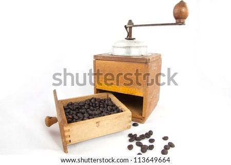 An old coffee grinder with coffee beans.
