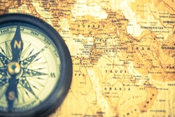 An old compass on vintage world map. Compass on map background. Close-up of ancient boat compass aboard on old world map. Focus on Middle East countries.