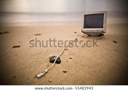 """an old computer abandoned on a beach during winter. It also reminds me the popular """"If you were stranded on an island what is the one thing that you would take with you?"""" - stock photo"""