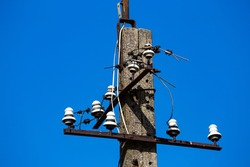 An old, concrete, unused electric pillarwith remains of porcelain insulators. Photo taken on a sunny day.