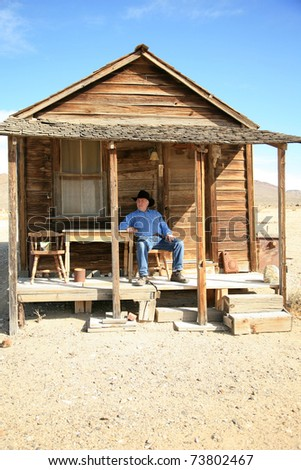 an old cowboy sits on the porch of his home after a hard day of ropin and riding the range