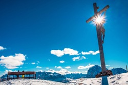 An old crucified Christ on the top of the mountain in italian alps during winter season