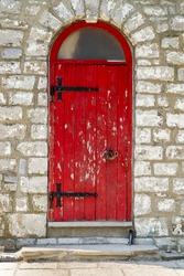 An old curved top red door with peeling paint and black hinges and handle.