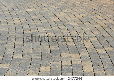 An old curved walkway made of pavers.