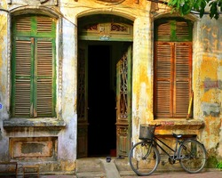 An Old, Decaying House with open door and shutters on the windows and a bicycle in Hanoi, Vietnam. Image by Kevin Hellon.