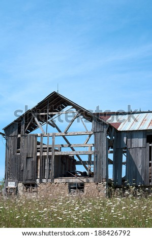 An old dilapidated wood barn in the process of falling down from neglect.