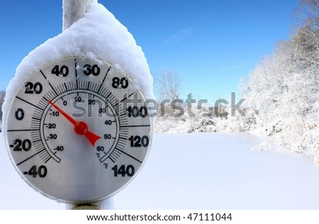An old dirty thermometer on a pole in front of a frozen over ice skating pond showing the temperature for the skaters