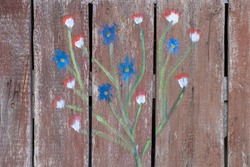 An old door with a cute floral ornament. Light burgundy aged, faded wood with stains. Textured background.