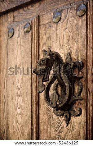 An old doorknocker in a wooden door in Pedraza, Segovia (Spain)