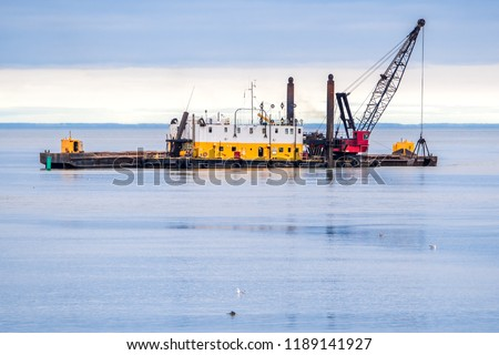 An old dredging barge in the ocean. Barge is yellow and white with a red crane on the deck. Scoop is being lowered into the water. Dark overcast sky.
