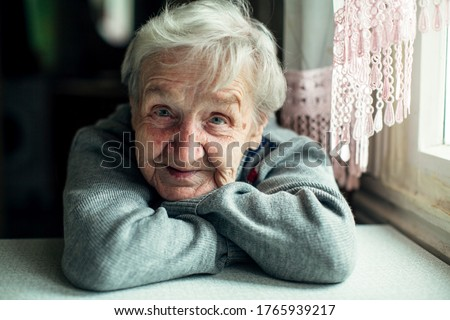 An old elderly woman, smiling portrait, looking at the camera, sitting in the kitchen.