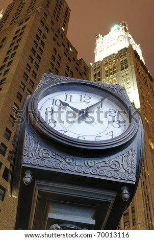 An old fashion clock in downtown Manhattan with skyscrapers behind it.