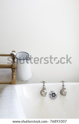 an old fashioned bathroom with bath and water jug