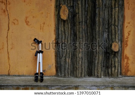 an old fashioned camera tripod and wall