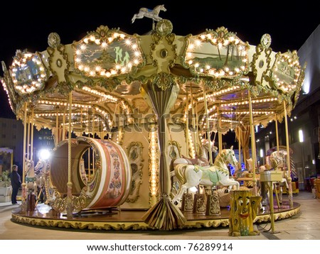 An old fashioned carousel at night.