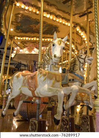 An old fashioned carousel at night. Detail of two horses