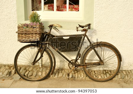An old fashioned delivery bicycle leaning against a wall in the UK