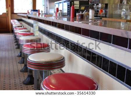 An old-fashioned diner with a tile floor and art deco style bar stools. Stock photo ©