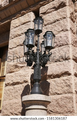 An old fashioned lamp post out the front of a historic building