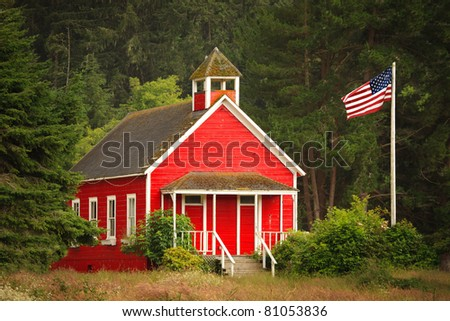 An old-fashioned little red schoolhouse in a forest area, with an American flag to the side.
