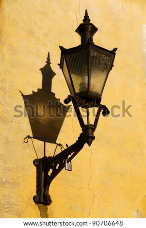 an old fashioned street lamp is hanging on wall in Old Town of Tallinn