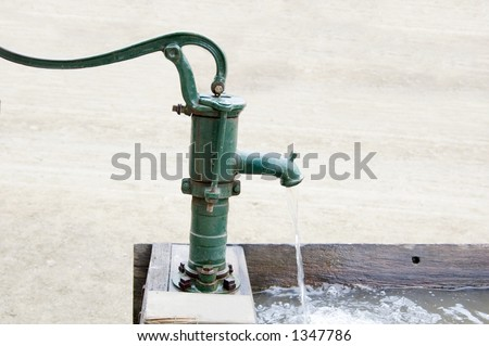 An old fashioned water pump above a drinking trough.