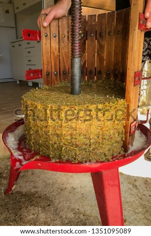 An old fashioned wooden barrel shaped grape press with the side removed and the pulp from the pressed grapes
