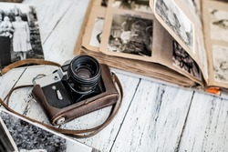 An old film camera and family album on a white wooden background among vintage family photos