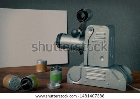 An old filmstrip projector points the lens at a white screen, with films next to it