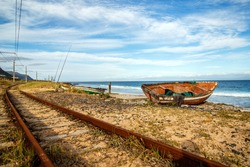 An old fisherman's boat, facing the ocean, left to decay near the shoreline, next to a railway track.