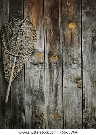 An old fishing net hanging on rustic wooden wall - stock photo