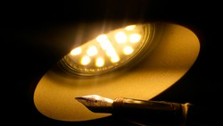 An old fountain pen featuring a golden metal nib illuminated by the warm yellow light of a LED lamp in the conical form of a dome ; allegorical image for inspiration in literacy or revelation