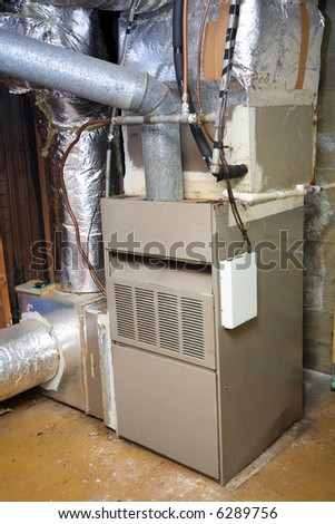 An old gas furnace in a dirty basement.