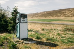 An old gas station for cars stands in a field, an abandoned gas station