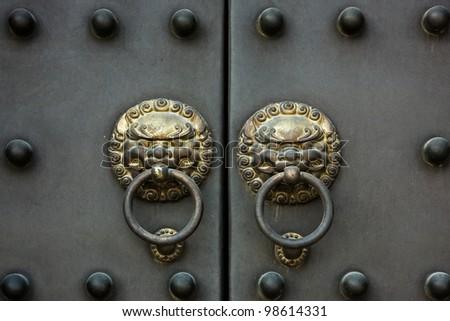 an old golden Chinese door handle on a heavy metal door
