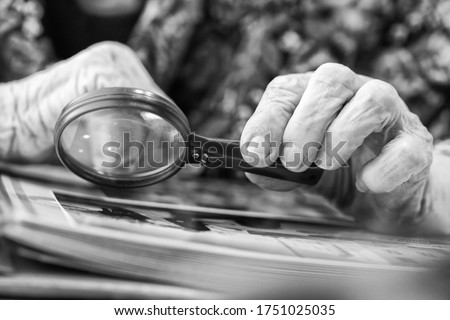 An old grandmother examines a book at the table with a magnifying glass Foto d'archivio ©