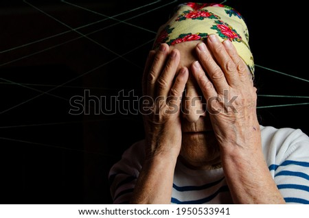 An old grandmother prays close-up. Prayer concept. Grandmother covered her face with her hands. An old woman in prayer. Grandmother's prayer. An aged mother prays. Old grandmother portrait photo.