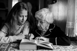 An old granny with a little girl reading a book.