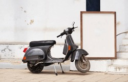 An old gray-black retro scooter is parked on a Zanzibar street near a frame or table. A place to write text.