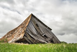 An old gray shed built from wood slats collapsed onto green grass in a summer countryside landscape