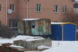 an old green iron container in rust and with a window stands on concrete blocks in white snow on a winter street near a brown house