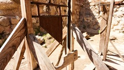 An old guillotine made of wooden planks and an iron blade. An ancient instrument of torture. Photo in the ancient castle against the background of stone walls